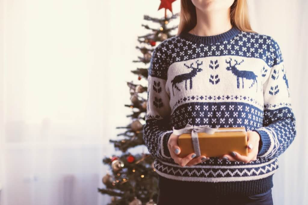 a woman wearing blue and white knitted sweaters with reindeer design