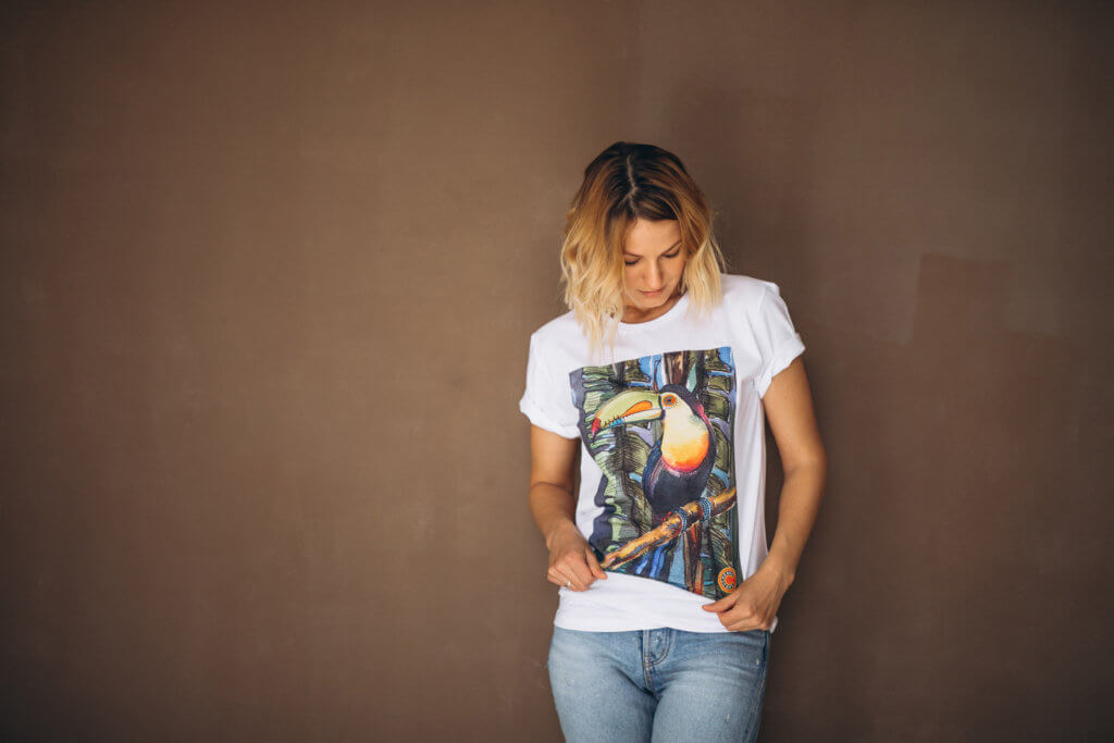 a blonde woman wearing a white shirt with a printed art of a bird