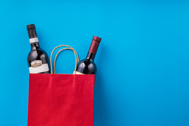 a red paper bag with two bottles of wine