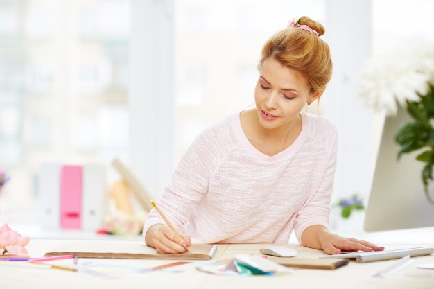 Woman holding a pencil over a sketchpad on a messy office table