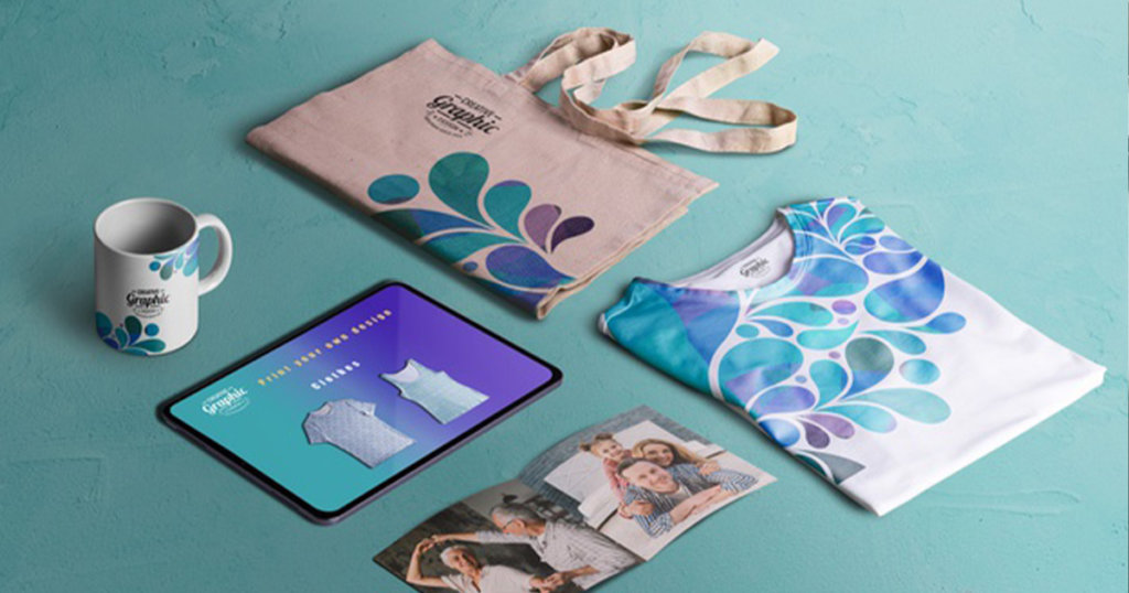 Mug, tablet, canvas bag, shirt, an open photo flat-laid side by side.