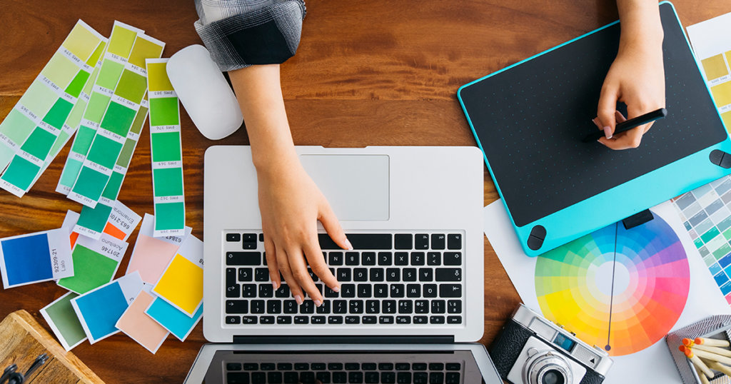 Hand holding a stylus over a drawing pad and another hand hovering the keyboard of a laptop beside a camera and color palettes